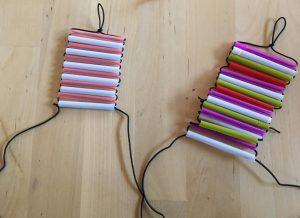 Siguiente paso: Introduce cada extremo de la goma por los orificios de la pajita.
