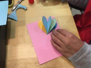 Siguiente paso: pega los corazones en la parte de arriba de la cartulina como si fuesen un abanico.