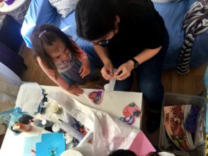 Nuestra trabajadora social, María Alonso, guía unas manualidades en uno de nuestros alojamientos gratuitos.